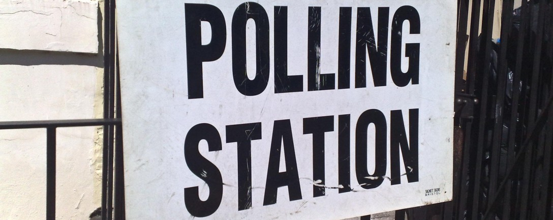 """Polling Station"" sign attached to black metal railings"